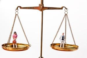 Mann und Frau auf Waage.Symbol Gleichheit